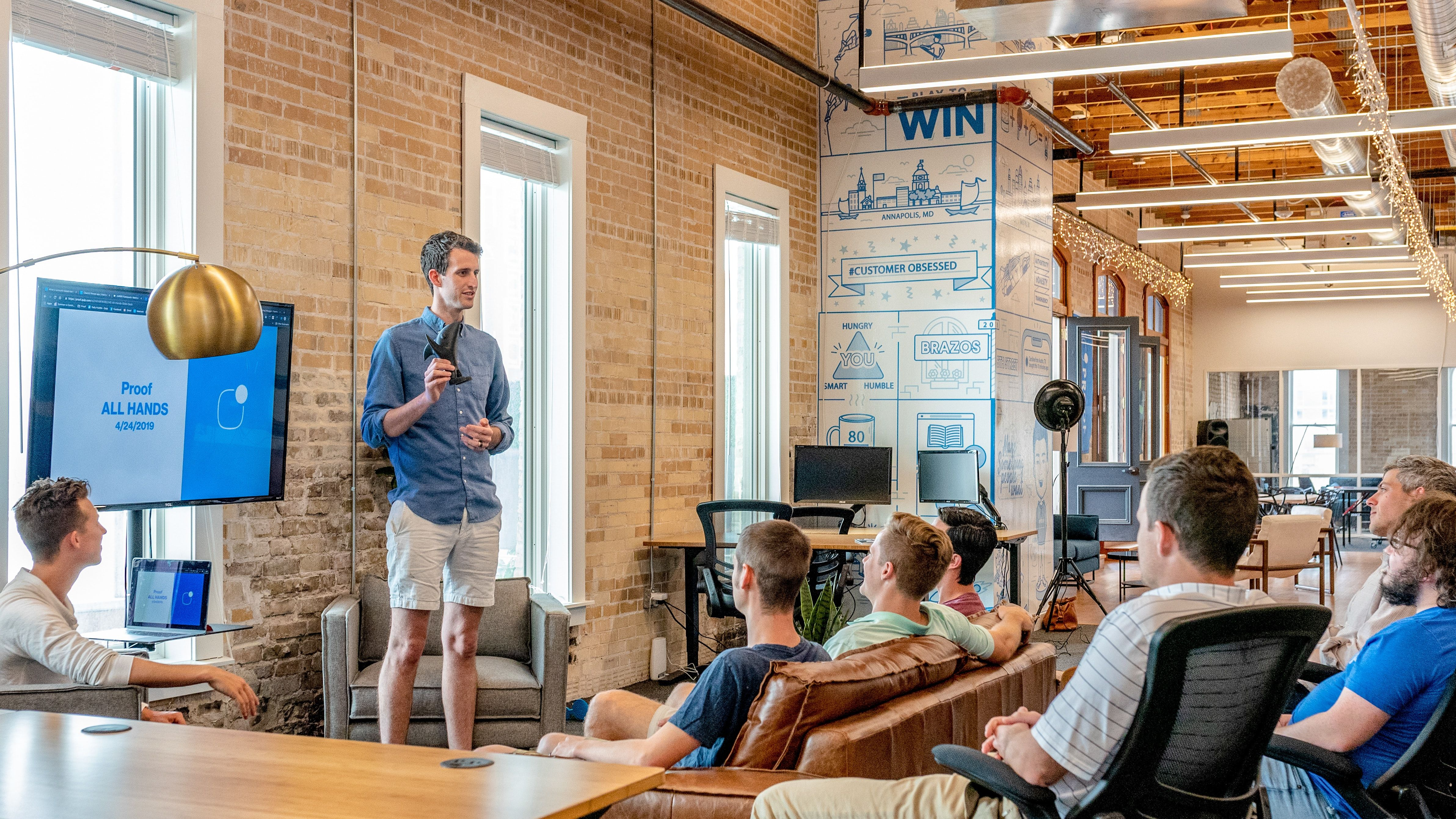 یک مرد در کنار صفحه نمایش بزرگ در حال حرف زدن است و چند مرد مقابل او نشستهاند