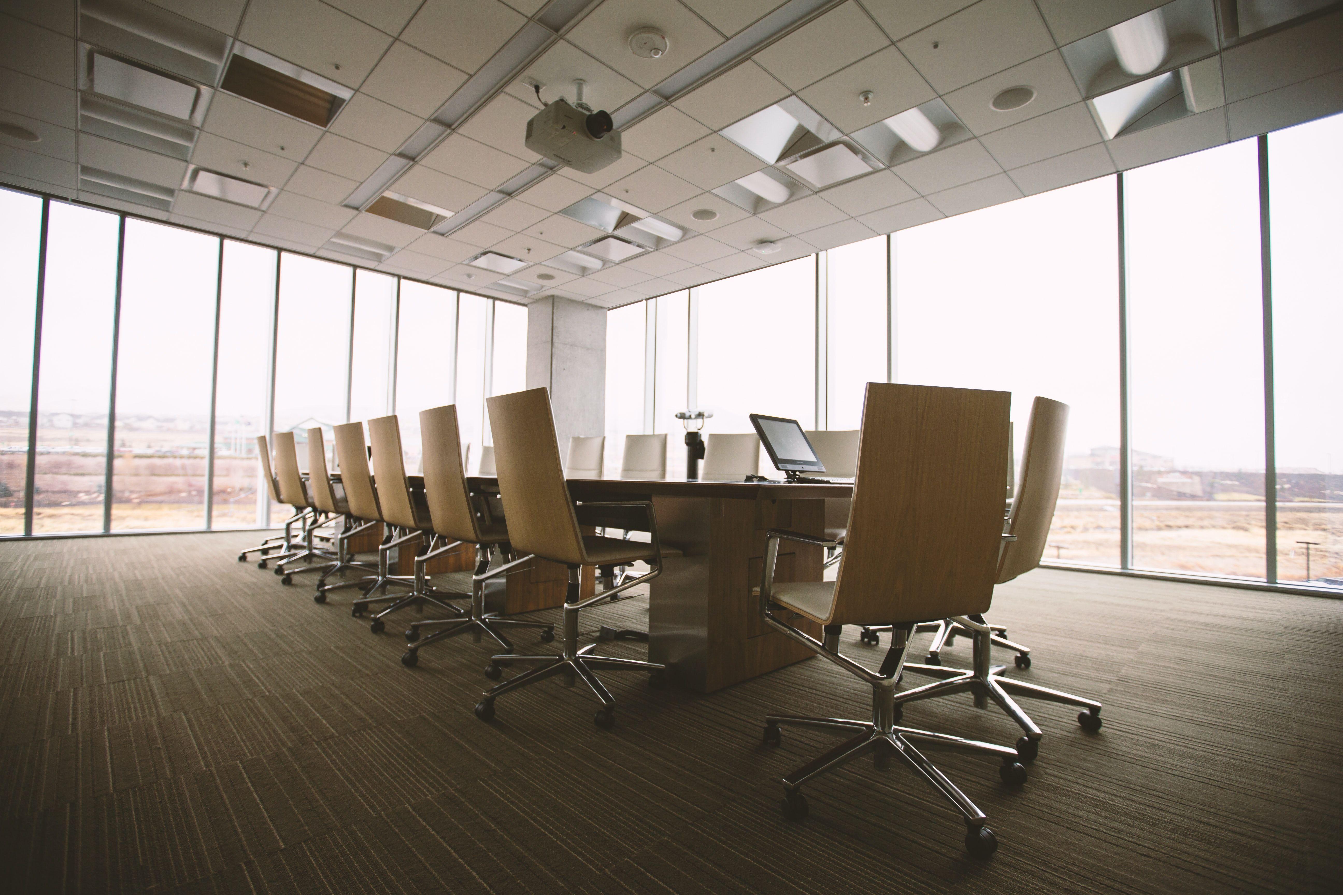 یک میز جلسه بزرگ و تعدادی صندلی خالی در اطرافش