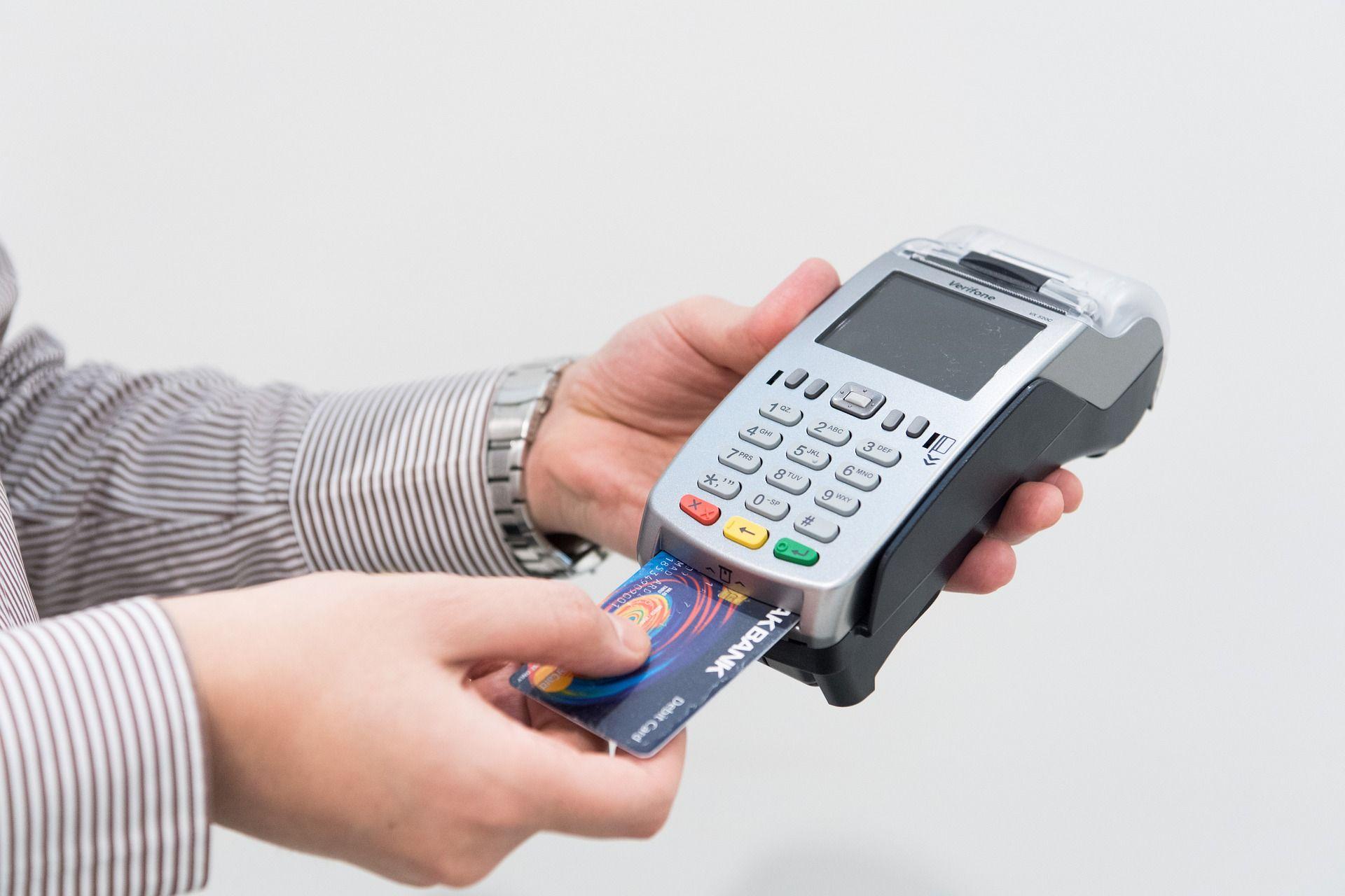 مرد یک دستگاه پوز و یک کارت بانکی در دست دارد
