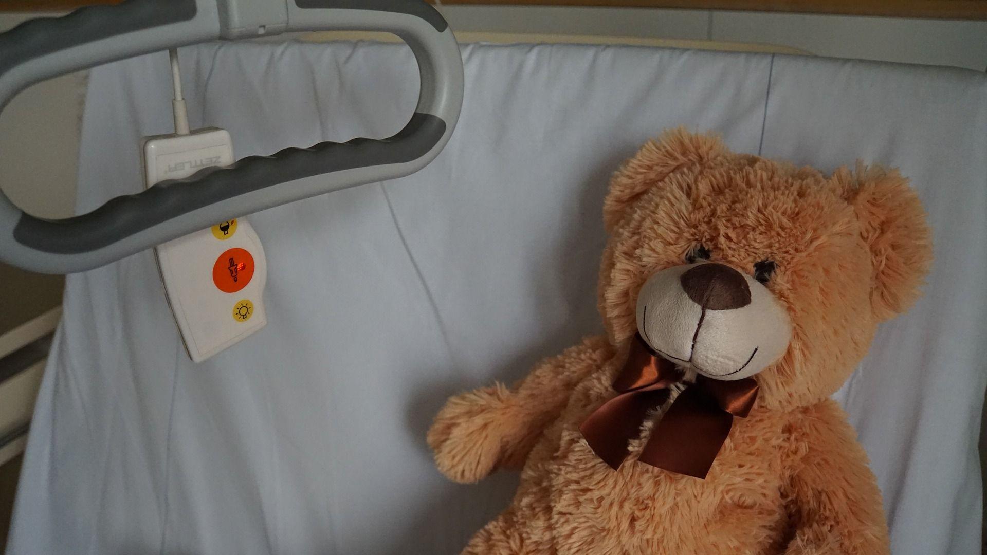 عروسک خرس قهوهای روی تخت بیمارستان