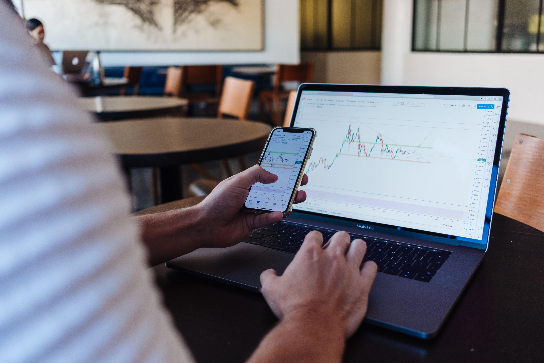 یک مرد در حال کار با لپتاپ و موبایل و تحلیل چارت بازارهای مالی