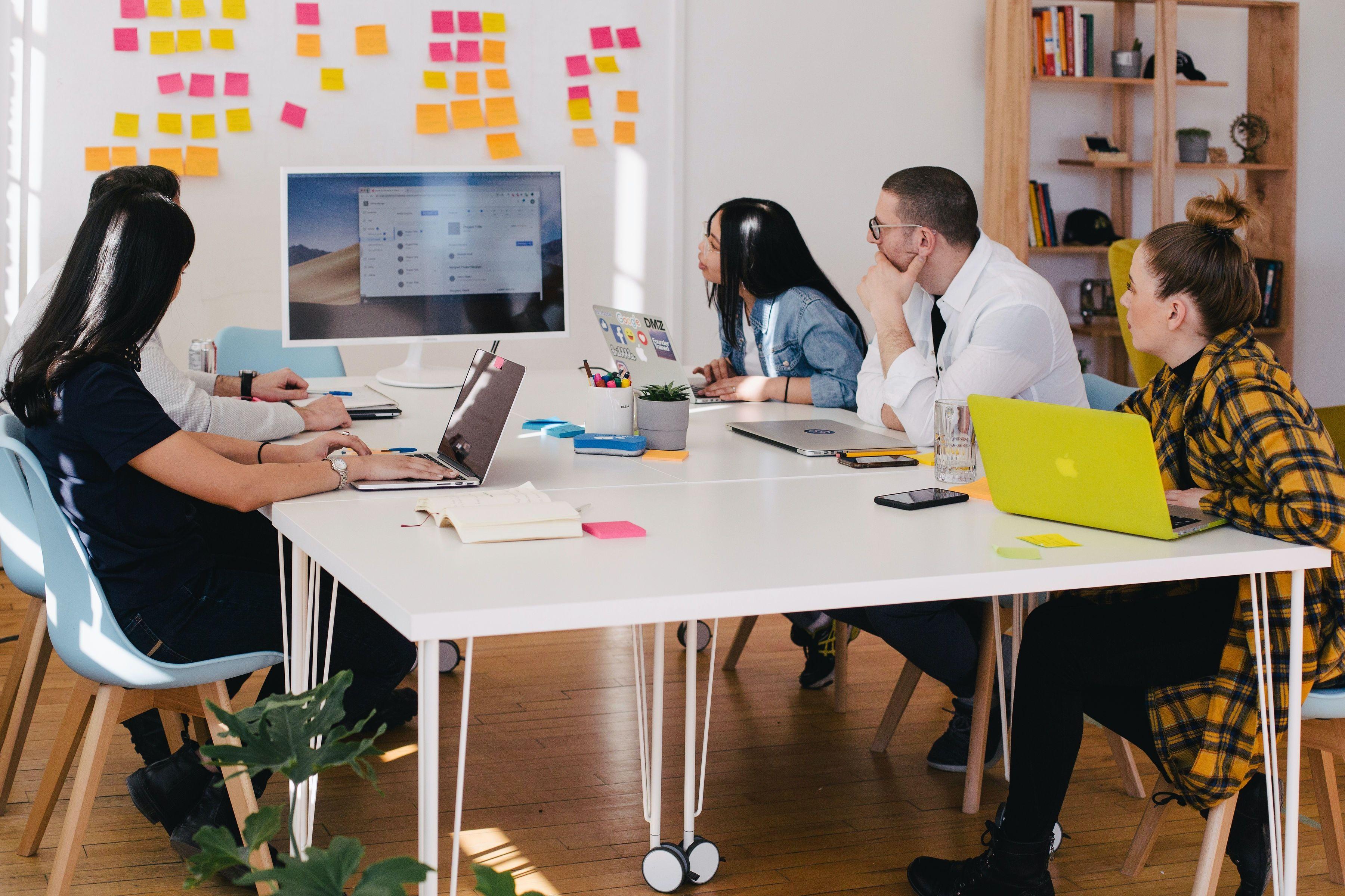 افراد دور میز در یک جلسهی کاری از کامپیوتر و تابلوی برنامهریزی استفاده میکنند