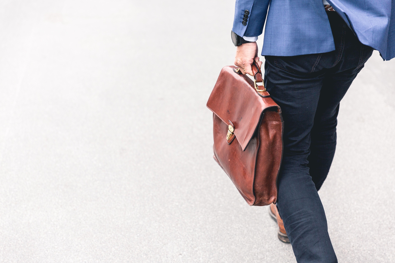 مرد با کت و کیف چرمی در حال راه رفتن است