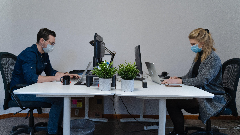 یک مرد و یک زن به خاطر کرونا در محیط کار با ماسک مشغول کار با کامپیوتر هستند