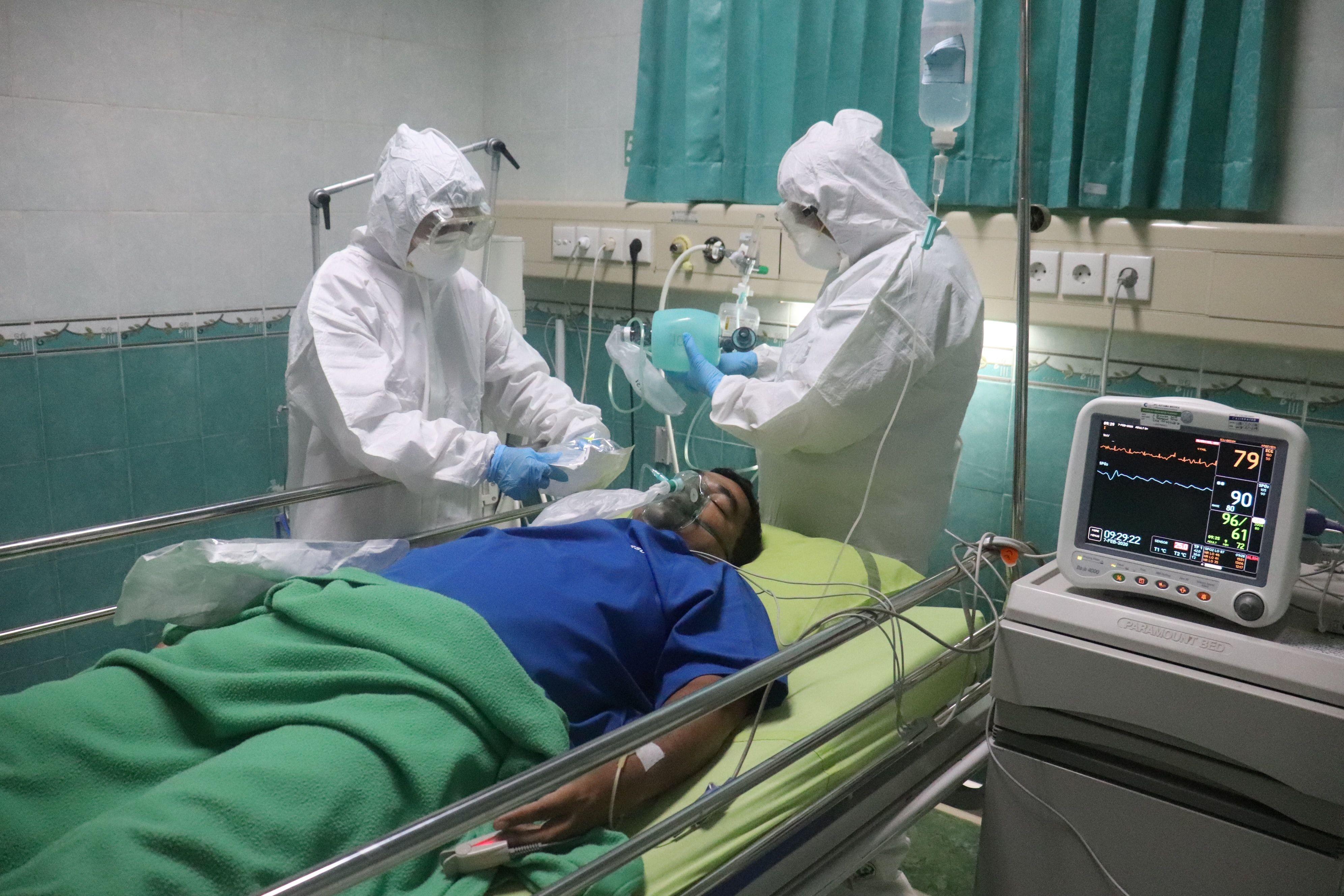 بیمار مبتلا به کووید روی تخت بیمارستان است و دو نفر از کادر درمان کنارش هستند