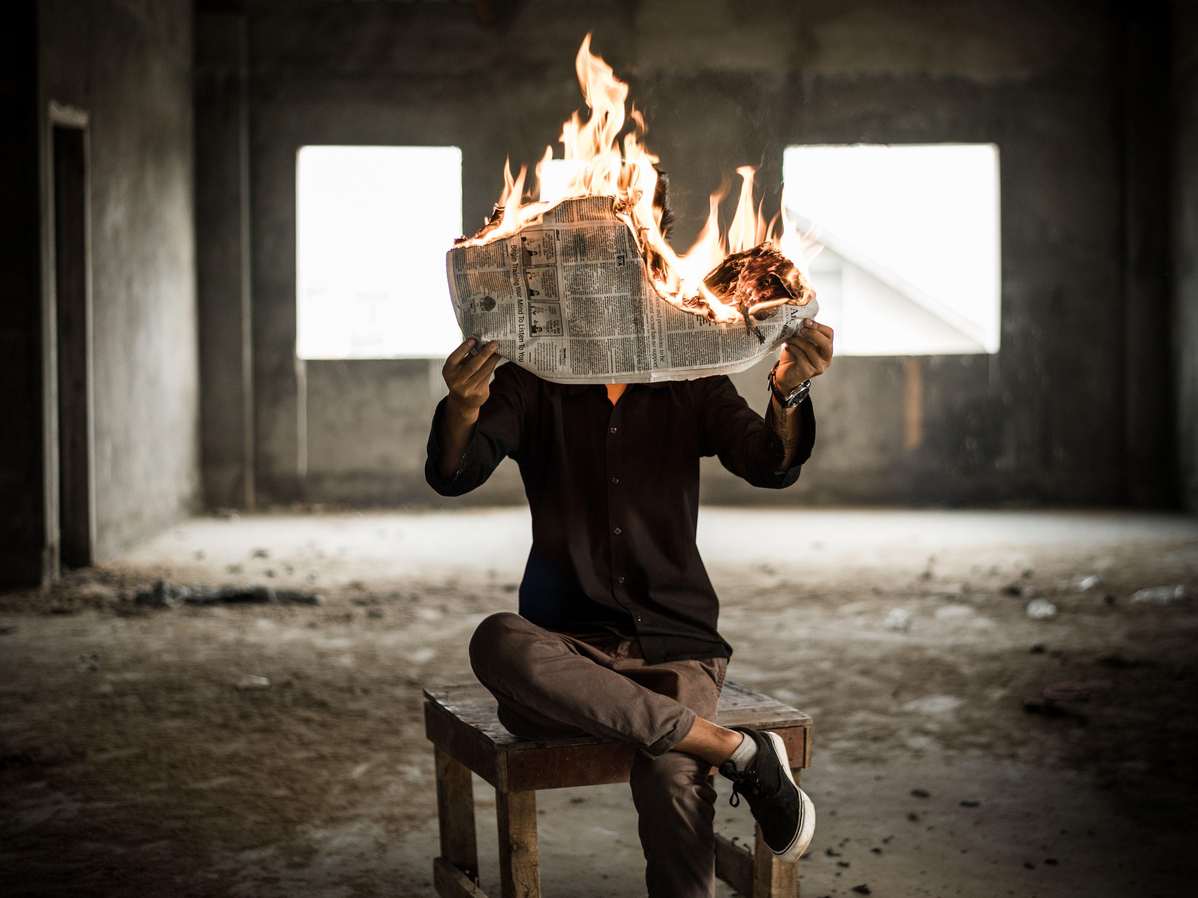 مرد در حال مطالعهی روزنامهای که آتش گرفته است
