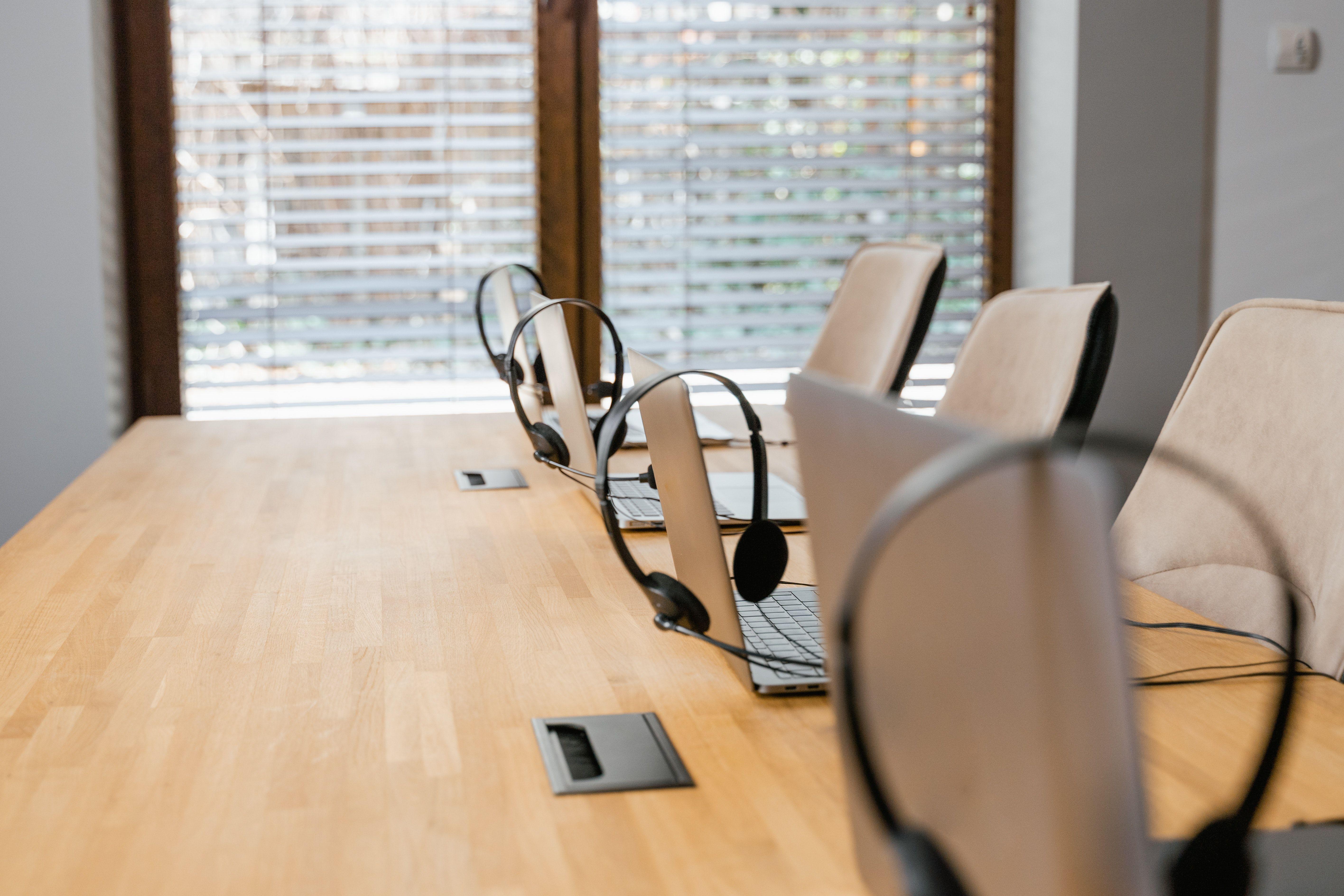لپتاپها و هدستها روی میز بخش پشتیبانی مشتریان یک شرکت