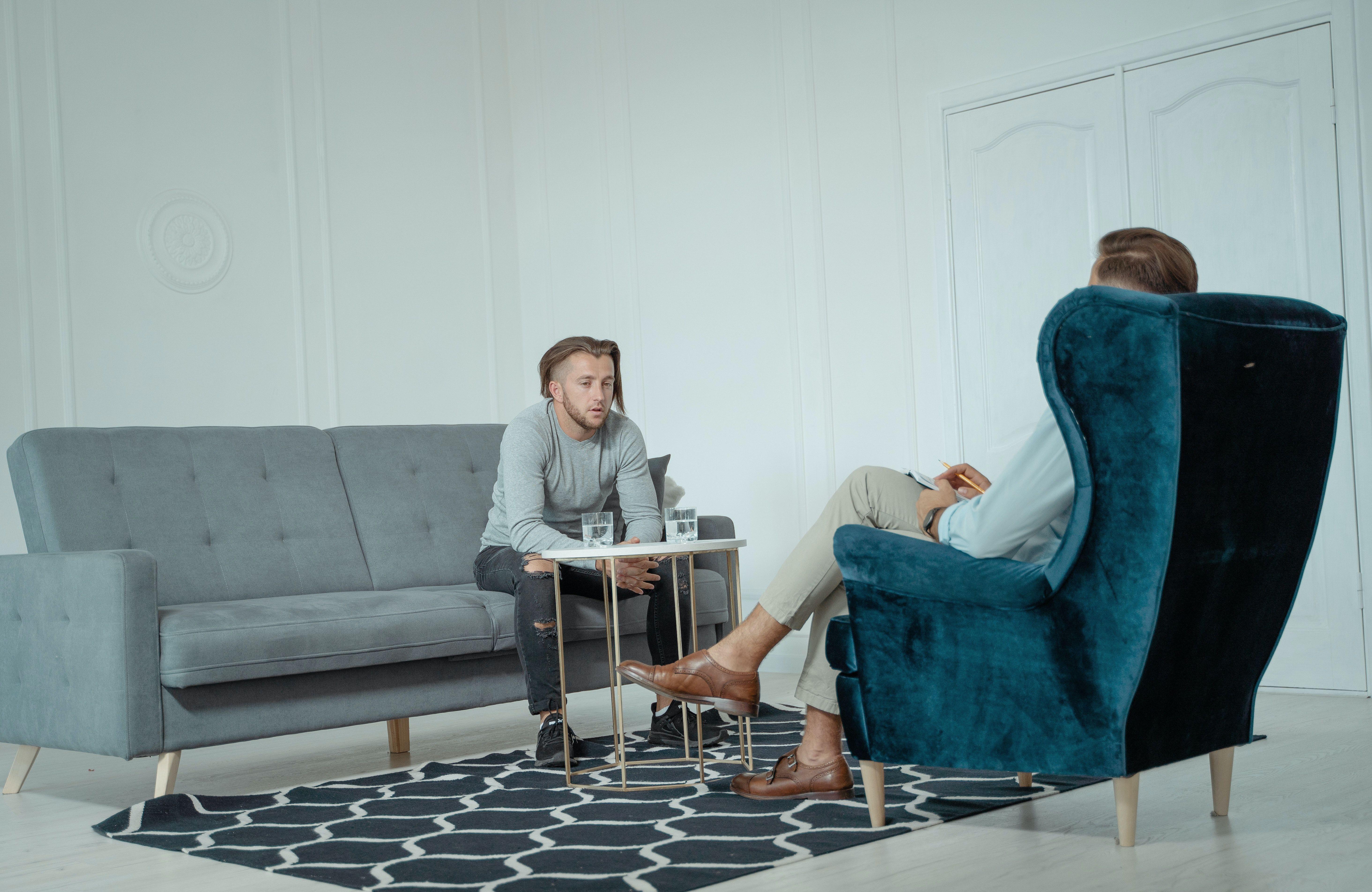 دو مرد نشسته بر روی مبل در یک جلسهی مشاوره روانشناسی