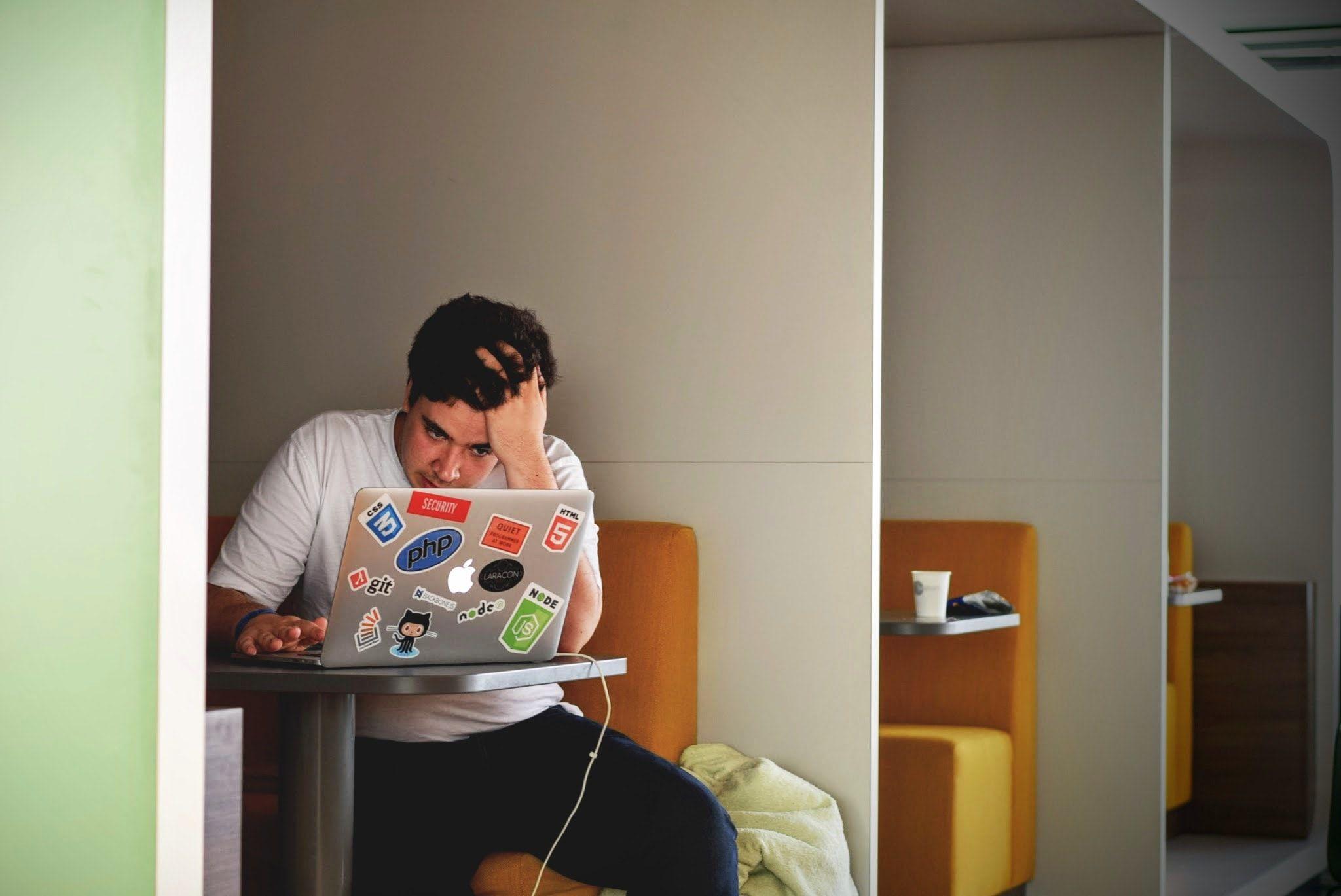 مرد با استرس درحال کار با لپتاپ